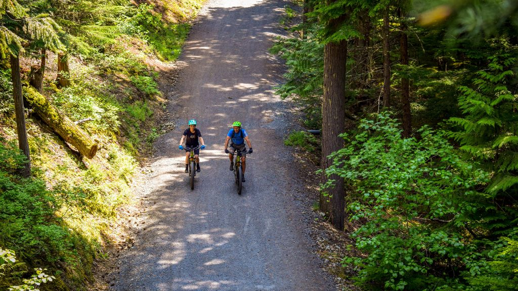 Two mountain bikers riding on a gravel trail around Lost Lake in Whistler, BC
