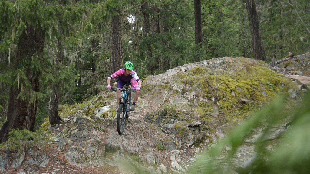 Mountain biker riding down a rock face in Lost Lake Park in Whistler, BC