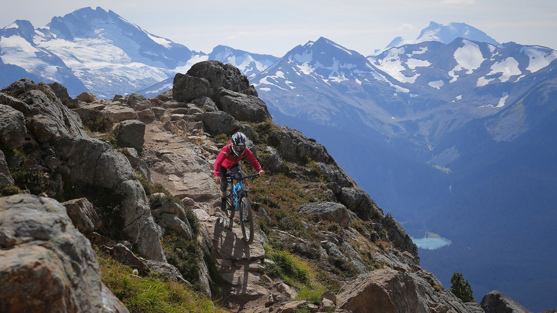 Mountain biker riding down the famous Top of the World trail in Whistler, BC