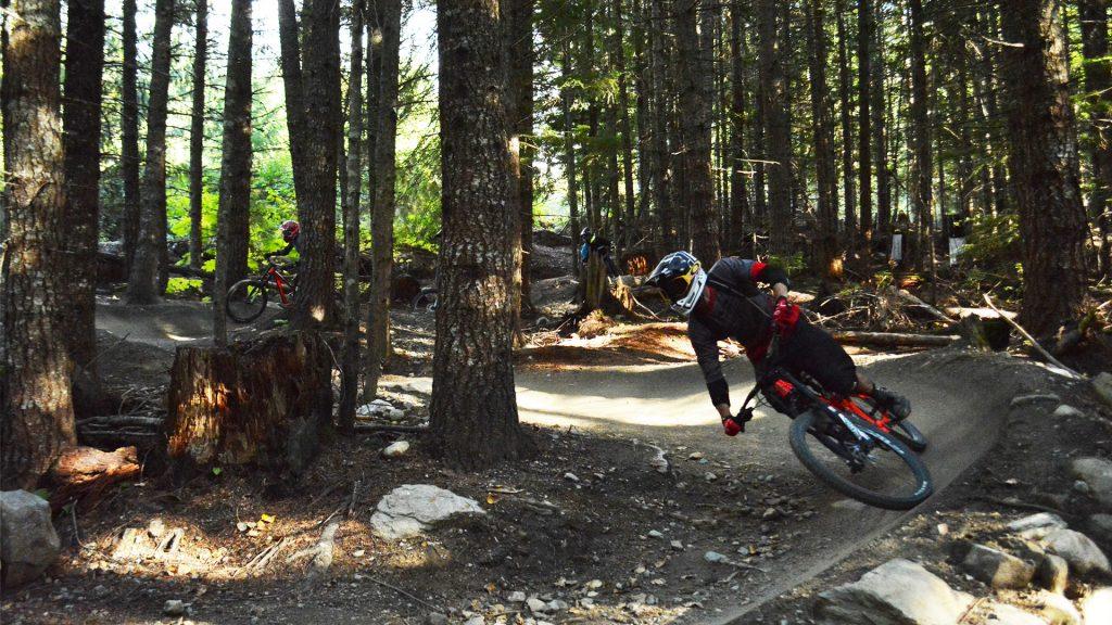 Mountain bikers descending on a Whistler Bike Park trail.
