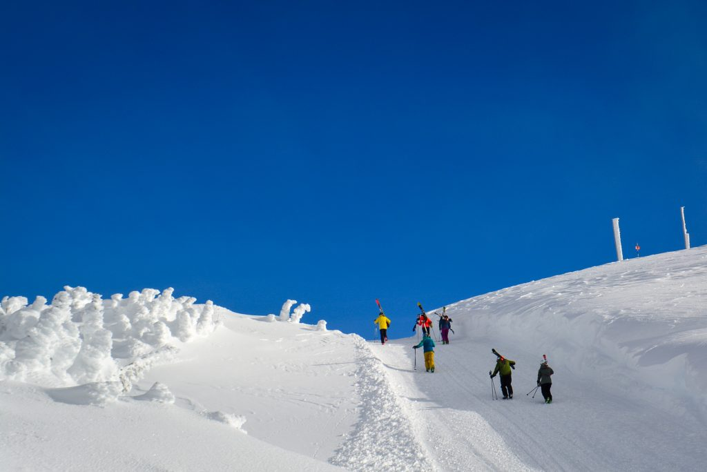 Skiers and snowboarders walking up Flute Bowl on Whistler Mountain